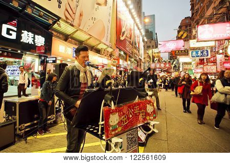 HONG KONG, CHINA - FEB 9: Rock musician sing a song during street performance in the bustling city on February 9, 2016. More than 47 million tourists visit Hong Kong annually