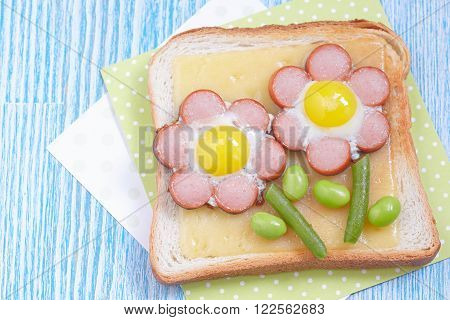Funny toast with cheese and flower made of sausages, green beans and quail eggs