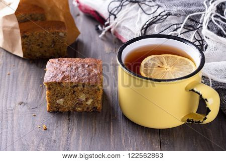 Homemade carrot and banana cake with nuts and spices a cup of tea with lemon on a wooden surface