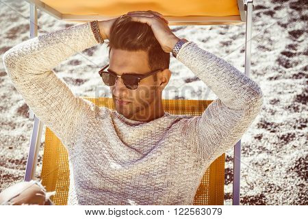 Young handsome man on beach sitting on deckchair resting and enjoying the vacation. Wearing light white sweater