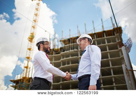 Two young architects in hardhats greeting each other with handshake
