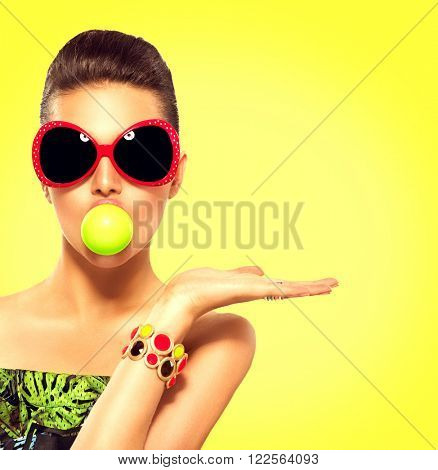 Beauty summer fashion model girl wearing sunglasses with green bubble of chewing gum and bright makeup showing empty copy space on the open hand palm for text over yellow background. Beautiful woman