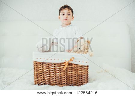 boy hid behind a basket with soft toys. playing
