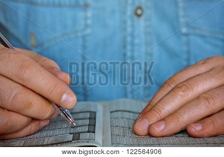 Closeup of two male hands holding a pen over the printed paper
