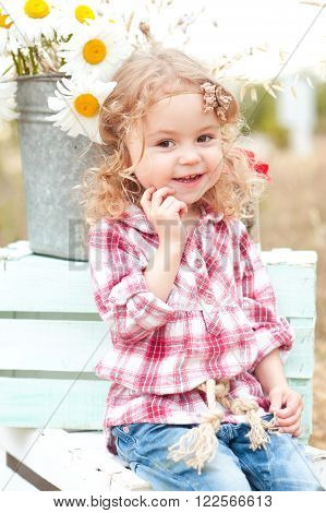 Cute baby girl sitting on crates with flowers outdoors