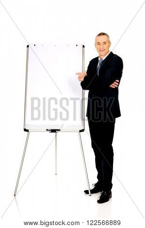 Male executive pointing on flip chart