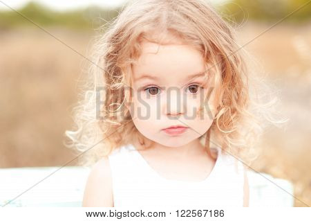 Cute baby girl with blonde curly hair outdoors. Little girl 2-3 year old.