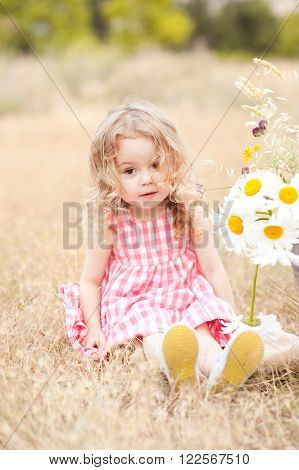 Cute baby girl 2-3 year old sitting with flowers outdoors. Looking at camera. Childhood.