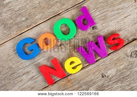 Colored letter magnets spelling text GOOD NEWS