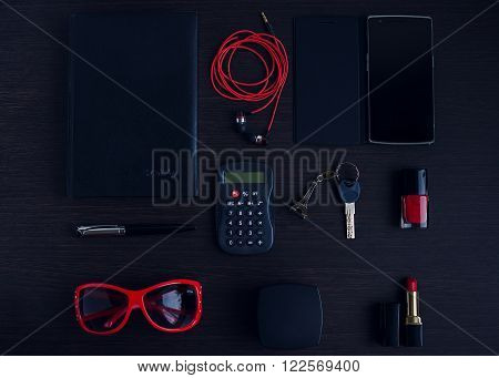 Women's red and black accessories on dark wooden background: sunglasses powder compact lipstick pen diary phone nail polish calculator. Business woman concept. Fashion on the work. Flat lay.