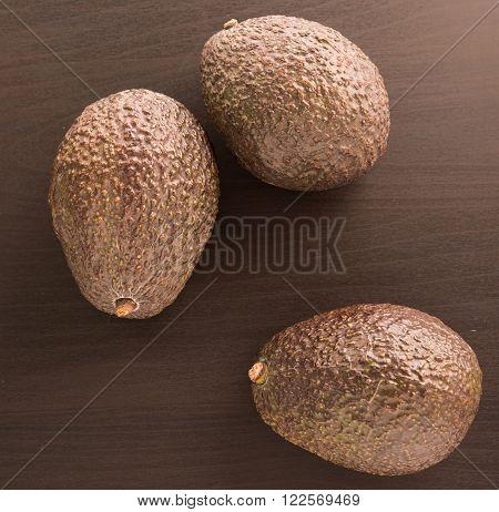 three fresh Avocados on a black background