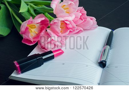 Tulips with pen and lipstick on empty notebook. Spring flowers. March 8th mother's day valentine's day International Women's Day congratulate. Toned image.