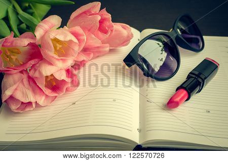 Tulips with sunglasses and lipstick on empty notebook. Spring flowers. March 8th mother's day valentine's day International Women's Day congratulate. Toned image.