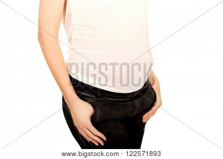 Pregnant woman with hands in pockets