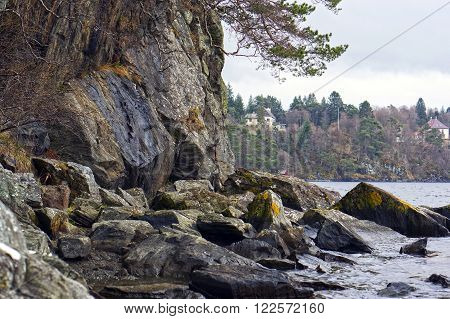 Norwegian fjords and mountains. Rocky shore, waves and trees. Bergen, Norway. May 06, 2013