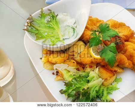 Viennese cutlet and fried potatoes served on white plate