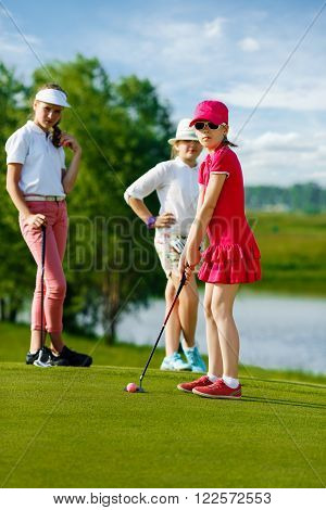 Kids playing golf by putter on green