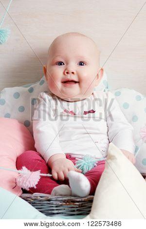 smiling baby girl playing among collorful pillows