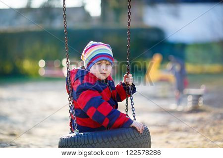 Funny kid boy having fun with chain swing on outdoor playground. child swinging on warm sunny spring or autumn day. Active leisure with kids. Boy wearing colorful clothes