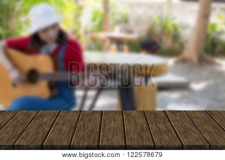 girl wearing red T-shirt and blue jeans sitting on wooden stool and playing guitar (blur background with wood table top for display or montage your product)