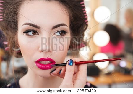 Makeup artist doing makeup and applying bright pink lipstick using brush in beauty salon
