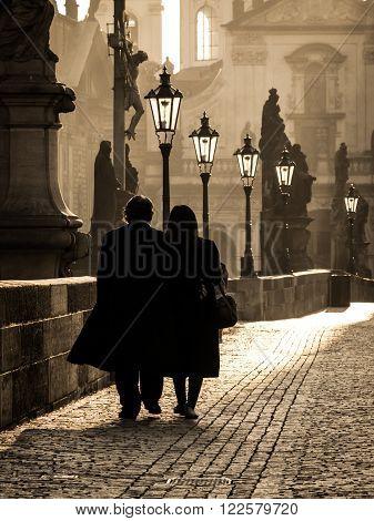 Couple walks on Charles Bridge in foggy morning, Prague, Czech Republic.