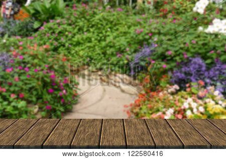 pedestrian walkway and beautiful flower in flowerbed in the garden (blur background with wood table top for display or montage your product)