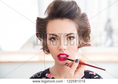 Portrait of young woman in curlers with makeup made by professional visagist
