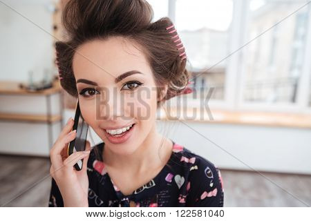 Cheerful beautiful young woman in curlers talking on mobile phone in beauty salon