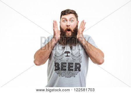 Surprised handsome bearded man with opened mouth over white background