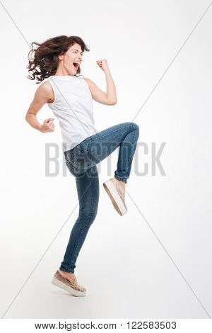 Full length portrait of a young woman celebrating her success isolated on a white background