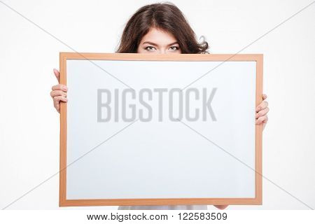 Young woman peeping from blank board isolated on a white background