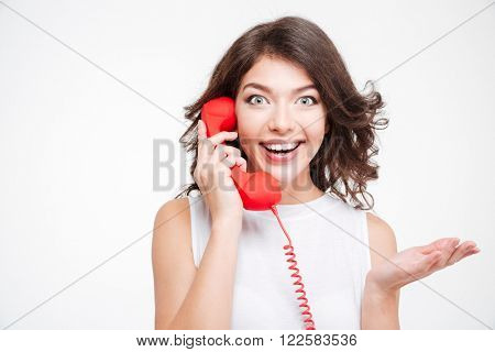 Cheerful woman talking on the phone tube and looking at camera isolated on a white background