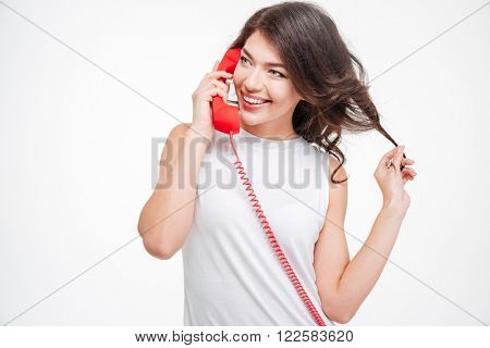 Happy woman talking on the phone isolated on a white background and looking away