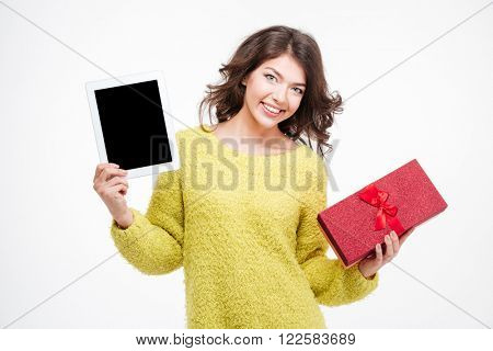 Happy woman showing blank tablet computer screen and holding gift box isolated on a white background