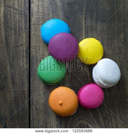 Colorful macaroons on wooden background from above