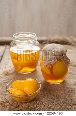 Preserved peach compote with whole peaches in glass jars on vintage wooden table background