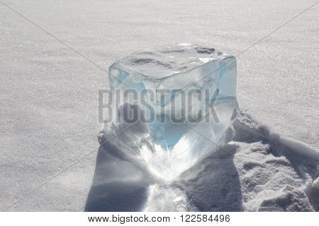 transparent cube of ice on the white snow