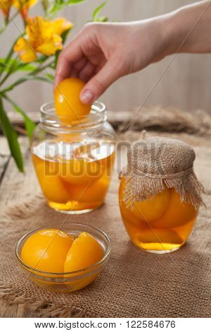 Natural canned peaches in glass jars with compote on vintage cloth background