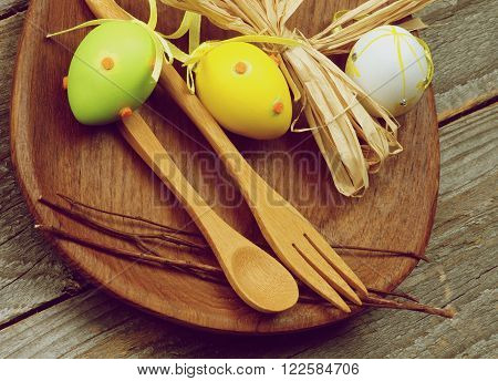 Easter Table Setting with Wooden Fork and Spoon Colored Eggs and Natural Branches on Wooden Plate closeup on Rustic Wooden background. Retro Styled