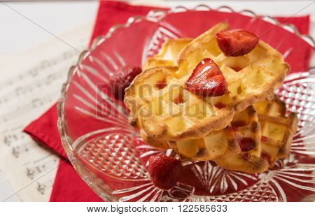 Cottage cheese waffles with strawberry sauce and a strawberry in a vase of glass on a red napkin and sheet music notation