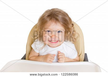 Happy smiling baby in the high chair. Kid waiting for favorite food or full-fed. Isolated on white background.