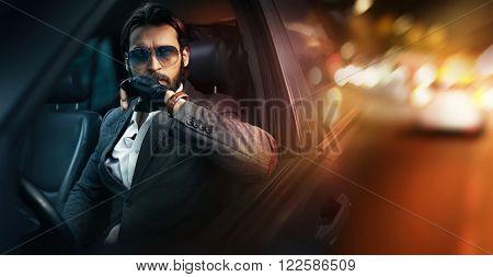 Outdoor portrait of elegant man driving a car