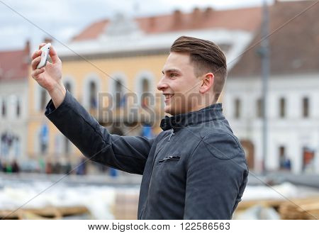Photo of a handsome and happy man taking a selfie