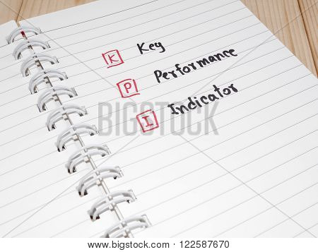 KPI (Key Performance Indicator) on white notebook with wood background (Business concept)