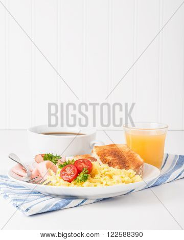 Portrait view of a plate of scrambled eggs and ham.