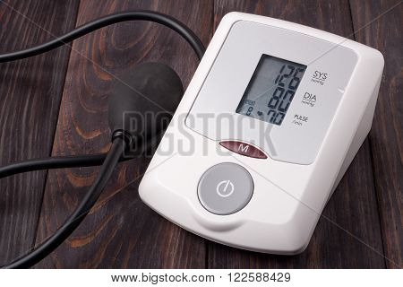 automatic blood pressure monitor on a wooden background.