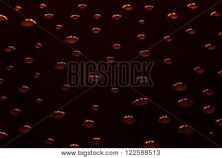 The shiny drops of water on a black background. The black background. The pattern.