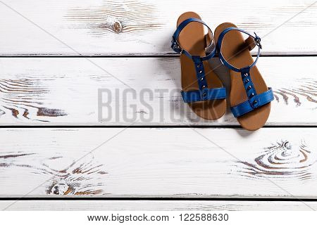 Close-up of woman's blue sandals. Female sandals on wooden shelf. Summer footwear with small buckle. Girl's shoes for summer.