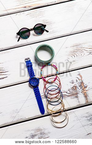 Woman's round sunglasses and accessories. Female accessories on wooden backround. Nice accessories for women. Tiny and bright.